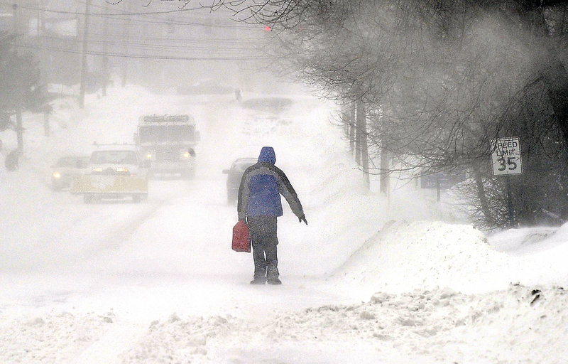A person carries a gas can down a South Portland street during a recent snowstorm. Readers say weather reports make too much of such routine hardships.