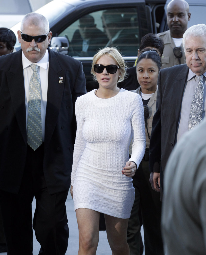 Actress Lindsay Lohan, center, arrives at the LAX Airport Courthouse in Los Angeles on Wednesday, to be arraigned on a felony grand theft charge.