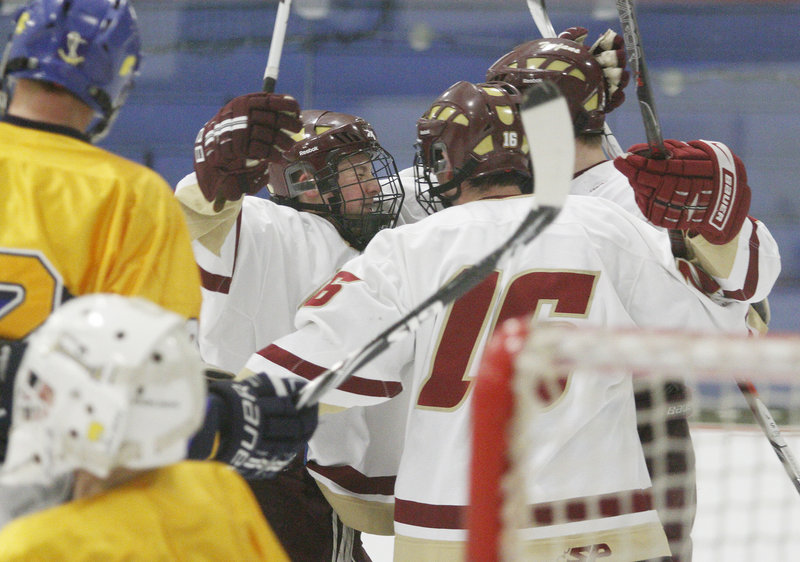 Greg Lodge, left, of Thornton Academy celebrates with teammates Wednesday night after Jonathan Herlihy scored in the second period to make it a 2-2 game – part of a 7-3 victory against Falmouth at the Biddeford Ice Arena.