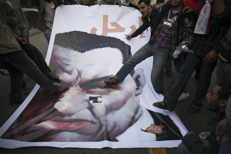 Anti-government protesters stomp on a poster of Egyptian President Hosni Mubarak on Wednesday outside the parliament building in Cairo. About 2,000 protesters waved huge flags outside parliament after moving four blocks from Tahrir Square, creating a second front in their bid to push Mubarak from power.