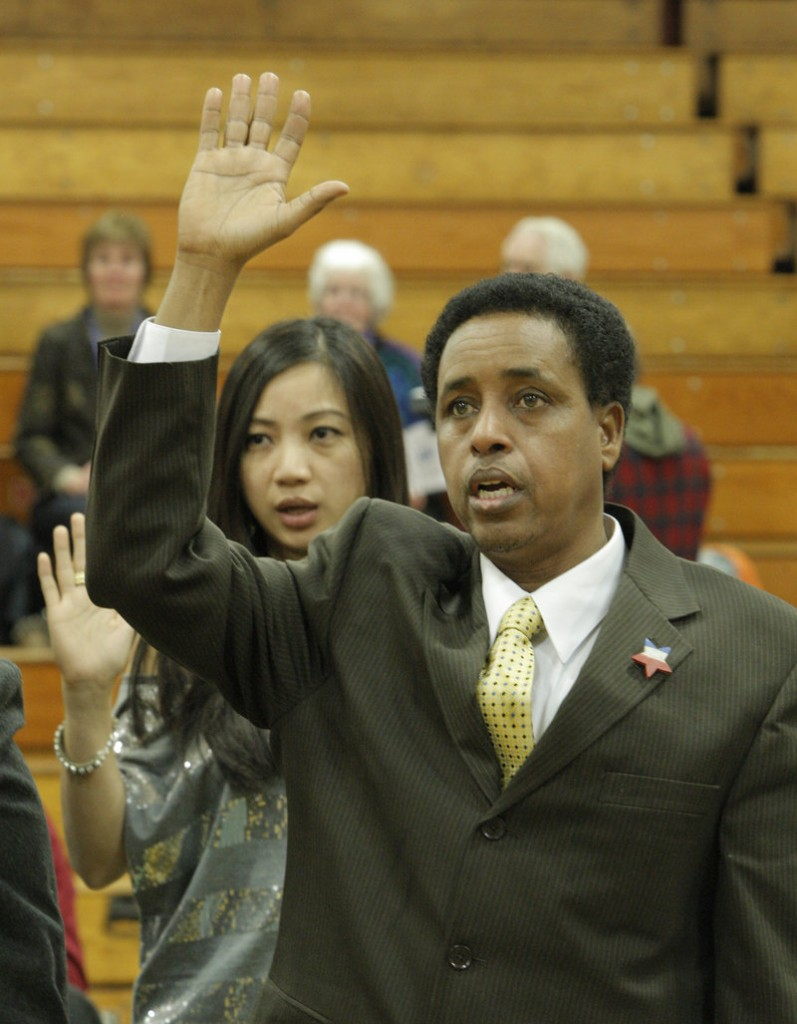 Abdulahi Abdi holds his hand high while being sworn in as a new U.S. citizen on Thursday in Falmouth.