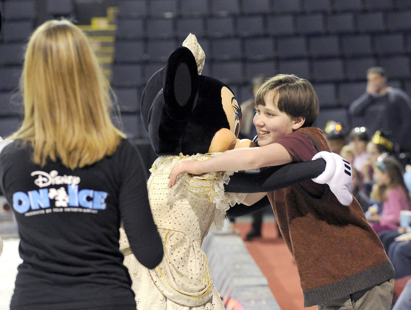 Peter Mahoney, 13, gets a hug from Minnie as performers from Disney On Ice conduct a skating clinic for Maine Special Olympics athletes at the Cumberland County Civic Center in Portland.