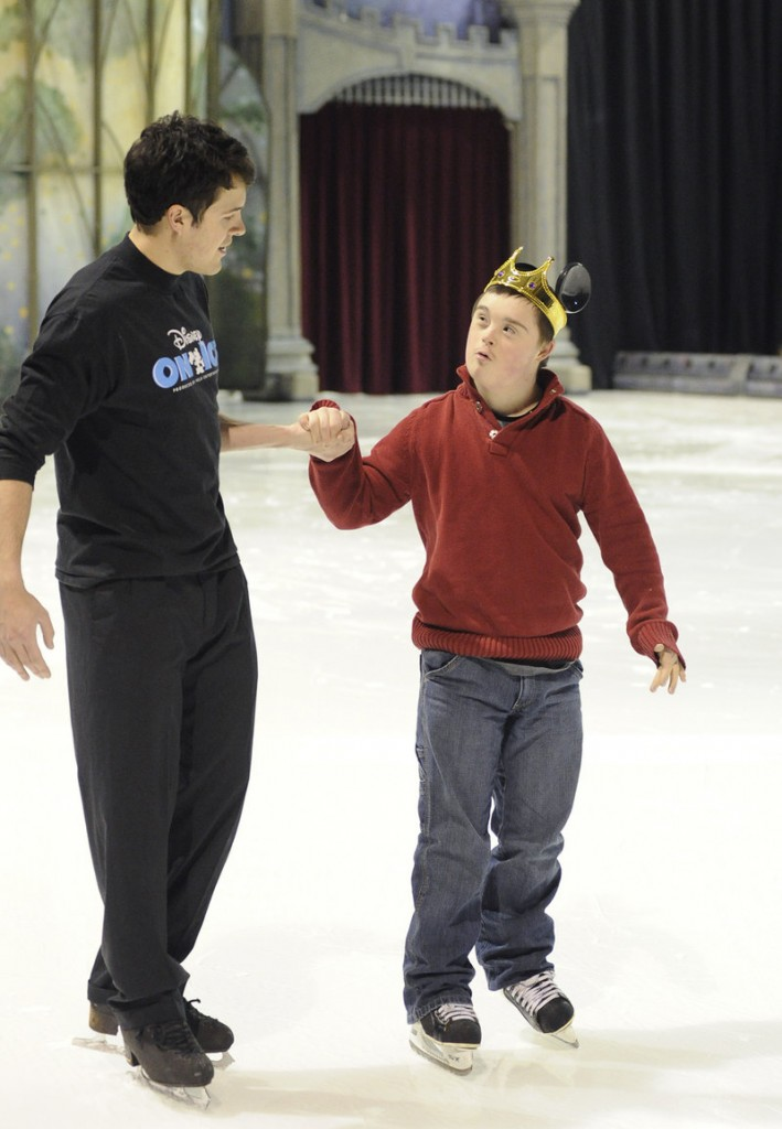 Disney on Ice's Conrad Giering skates with Caleb Dunlap, 15, of Gorham during Thursday's Special Olympics clinic.