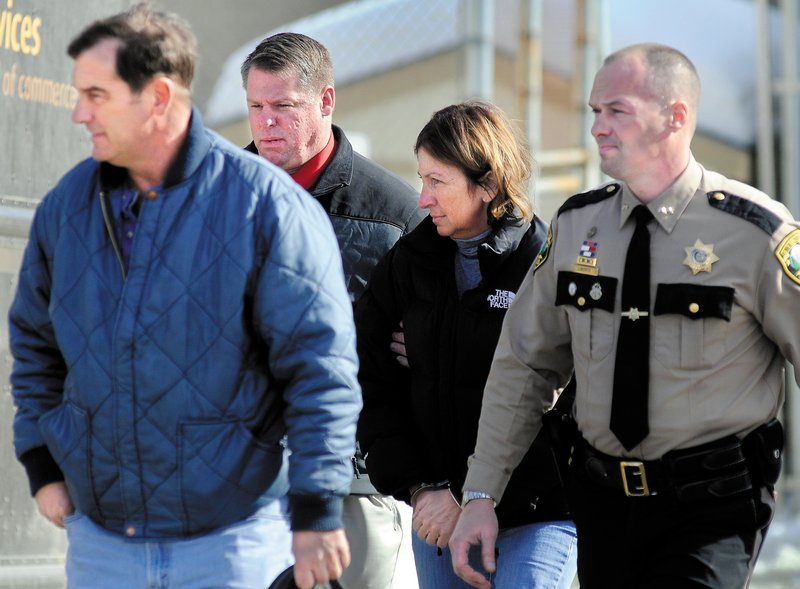 Carole Swan is led to Kennebec County jail Thursday after being arrested at the Sheriff's Department. She was released on bail pending a May 24 hearing.