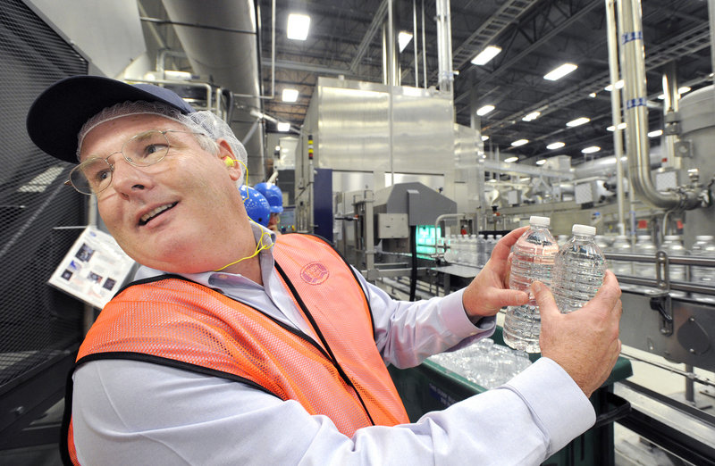 William Maples, supply chain director for the Northeast for Nestlé, shows two bottles that were overfilled and rejected at the Poland Spring bottling plant in Hollis.