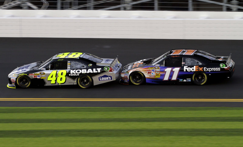 Jimmie Johnson, left, leads Denny Hamlin around the track at Daytona International Speedway during a practice session Friday. The two drivers race for Joe Gibbs Racing, which is celebrating its 20th year of racing and harbors hopes of winning another NASCAR title.