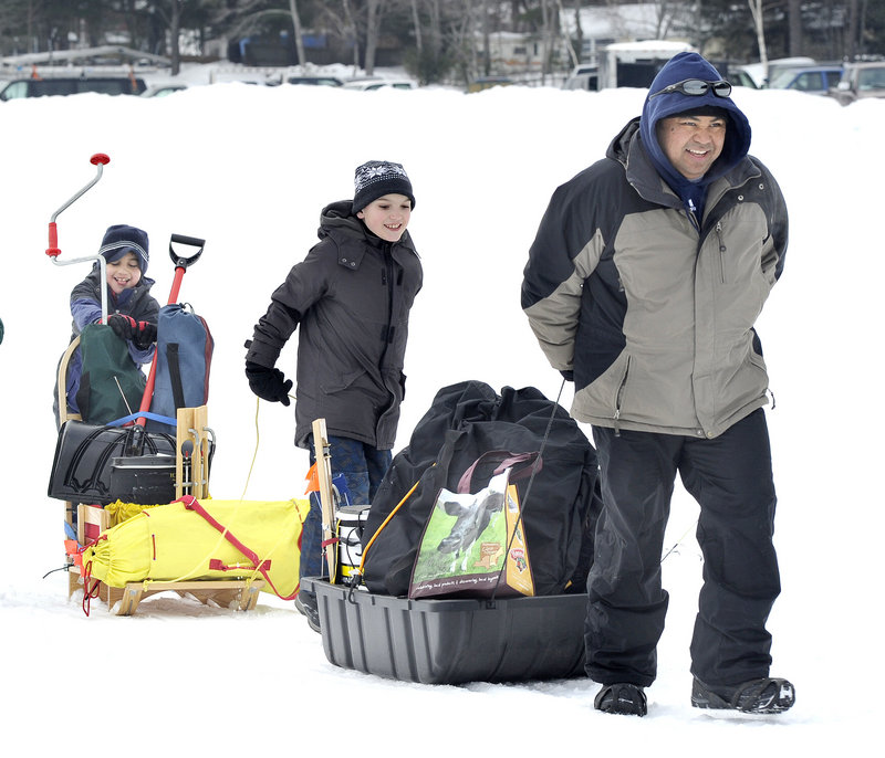 Rick San Pedro, right, of Topsham hauls ice fishing gear onto the lake with Alex Bryant, 10, center, and Will San Pedro, 9, to set up for the derby.