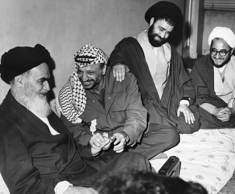Ayatollah Ruhollah Khomeini, left, smiles with Palestinian leader Yasser Arafat in Tehran. The Ayatollah's son has his hand on Arafat's shoulder. The uprising that toppled the shah of Iran took a year, paralyzed the country and grew violent.
