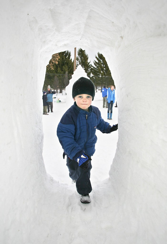 Thomas Healey, 4, of Falmouth climbs through a tunnel at the snow sculpture area during Saturday's Portland WinteRush.
