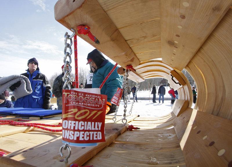 Sledders get a tag for their toboggan after it has been inspected and deemed ready to ride in the championships on Saturday.