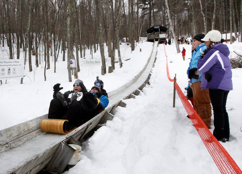 Coby Lerner of Baltimore, Md., screams as he races down the track with his father Mark and brother Tyler, in back, during the 21st annual U.S. National Toboggan Championships in Camden on Saturday. Some sledders believe that screaming during the run can make them go faster.