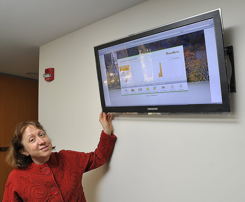 Catherine Longley, a Bowdoin administator, shows the Lucid Building Dashboard, an energy monitor that displays the Btus being consumed by the heating system at Thorne Dining Hall on campus.