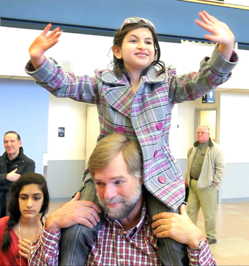 Sitting on Doug Rogers' shoulders, Noora Afif Abdulhameed waves to friends on Monday before boarding a plane home to Iraq.