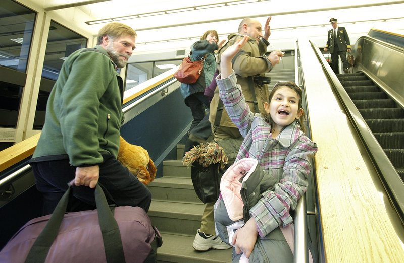 Noora Afif Abdulhameed waves to friends on Monday while walking upstairs at the Portland International Jetport to board a plane for the return trip to Iraq. At left are Doug Rogers and his wife, Susi Eggenberger, who helped to organize Noora's trips to Maine.