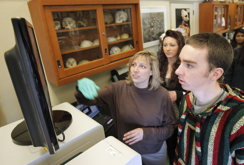 Jennifer Jamison and Deering sophomore Billy Farrell look at an image on a monitor connected to an electron microscope in a biology class at the high school Tuesday. Jamison is a microscopist and research associate at the University of Southern Maine.
