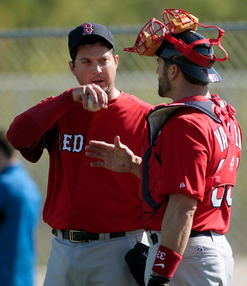 Josh Beckett, left, talks with catcher Jason Varitek at the Boston Red Sox player development complex in Fort Myers, Fla., Tuesday. It was the first official spring training workout for pitchers and catchers.