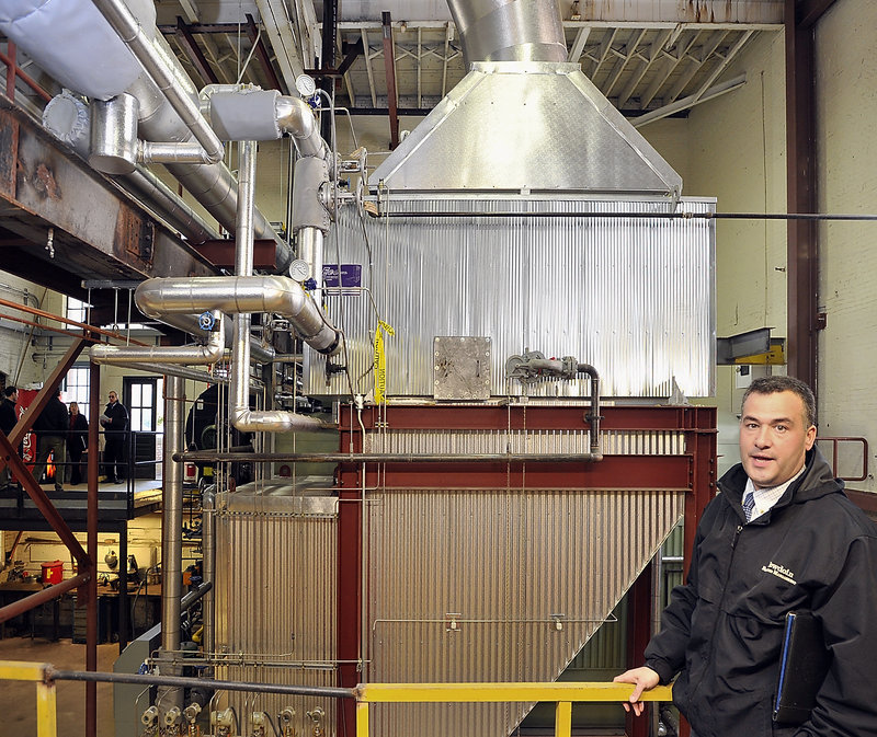 John Simoneau, capital projects manager in the facilities department at Bowdoin College in Brunswick, points out an addition to the campus' steam heating system that recovers heat from the boiler's exhaust, part of an overall commitment by the school to become carbon neutral by 2020.