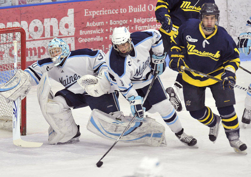 Maine goalie Dan Sullivan scurries back to his net Friday night as Mark Nemec clears the puck away from Brandon Brodhag of Merrimack. Sullivan earned a third straight shutout and is fewer than 14 minutes from Jimmy Howard's school record for minutes without allowing a goal.