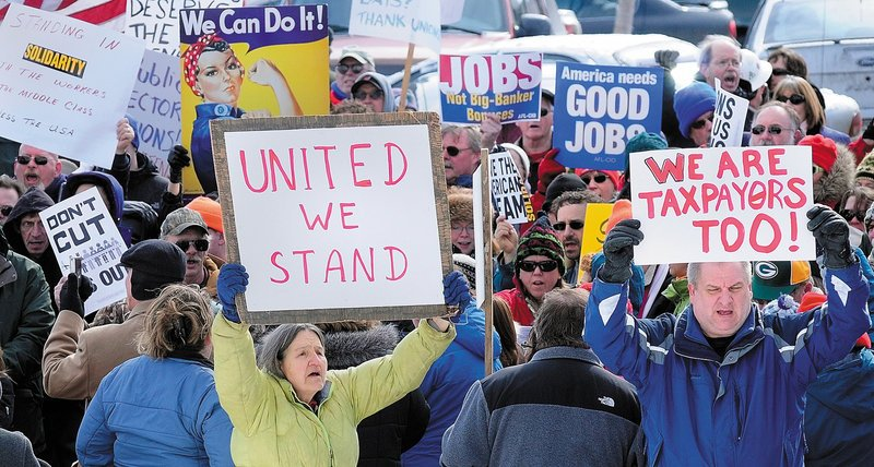 Demonstrators singing union songs and carrying signs gather in a parking lot on the south side of the State House in Augusta on Saturday. The rally was partly a reaction Gov. Paul LePage's proposal to reduce pension benefits for retired state employees and teachers, and partly to support unionized state workers in Wisconsin.