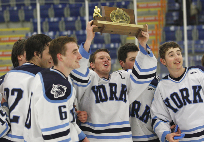 Anthony Figlioli hoists the state championship trophy while celebrating with teammates after defeating Brewer 4-3 in overtime. Figlioli scored the two goals including the winner.