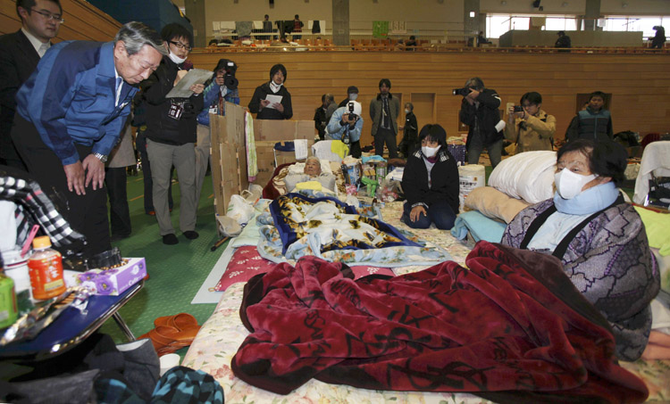 Norio Tsuzumi, vice president of Tokyo Electric Power Co., left, apologizes to evacuees at an evacuation center in Tamura of Fukushima Prefecture, Japan, today. Public sentiment is such that Fukushima's governor Yuhei Sato rejected a meeting offered by the president of Tepco, the utility that runs the Fukushima nuclear plant.