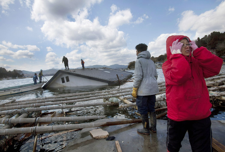 Reiko Kikuta, right, and her husband Takeshi Kikuta watch as workers attempt to attach ropes to their submerged home to try to pull it ashore with construction equipment on Oshima Island in northeastern Japan today. 9.0 Magnitude Earthquake; Destruction; Devastation; Disaster; Ea