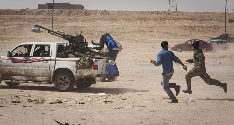 Libyan rebels flee as shellis from Gadhafi's forces start landing on the front line outside of Bin Jawaad, Libya, today.