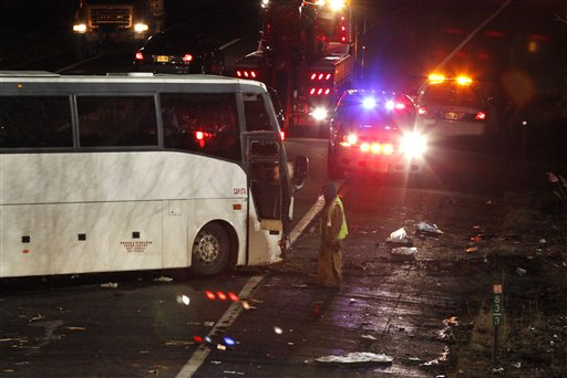In this March 15, 2011, file photo, a worker is seen next to a luxury bus that crashed on Exit 9 of the southbound New Jersey Turnpike, in East Brunswick, N.J. Deadly bus crashes over the past decade have claimed dozens of lives, including college baseball players in Atlanta, Vietnamese Catholics in Texas, skiers in Utah and, this month, gamblers returning to New York's Chinatown.