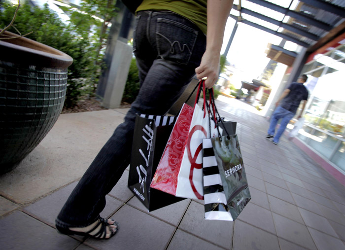 A shopper walks through a mall in Gilbert, Ariz., recently. A private research group says soaring prices in gas and other household costs pulled down consumers' confidence in March.