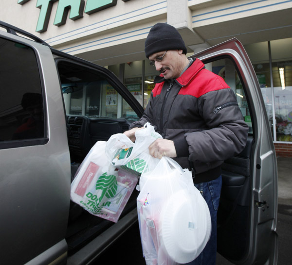 Larry Buckley leaves a Dollar Tree store in Batavia, N.Y. Consumer spending rises at fastest pace since October, led by purchases of autos and gasoline.