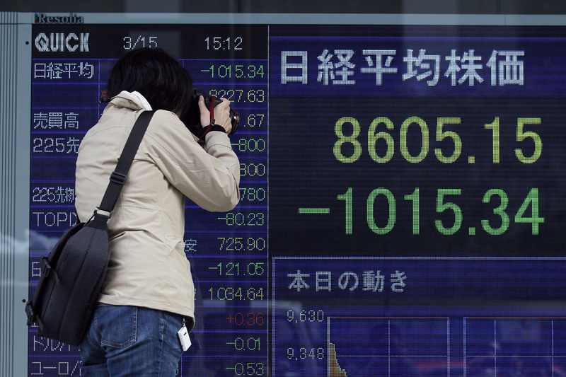 A photographer takes a photo of a stock price board in a street on Tuesday in Tokyo, Japan. Japan's Nikkei stock index nose-dived nearly 11 percent Tuesday as the earthquake-shattered country faced an unfolding nuclear crisis. 9.0 Magnitude Earthquake,Destruction,Devastation,Disaster,Earthquake,people,person,Ruin,Sendai Earthquake and Tsunami