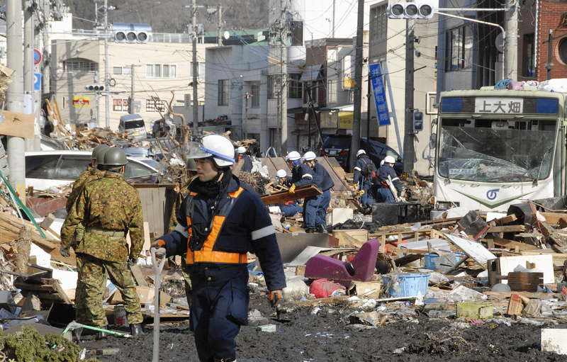 Japanese soldiers and rescue workers try to remove rubble on a street in Kamaishi, northeastern Japan, today, one day after a giant quake and tsunami struck the country's northeastern coast.