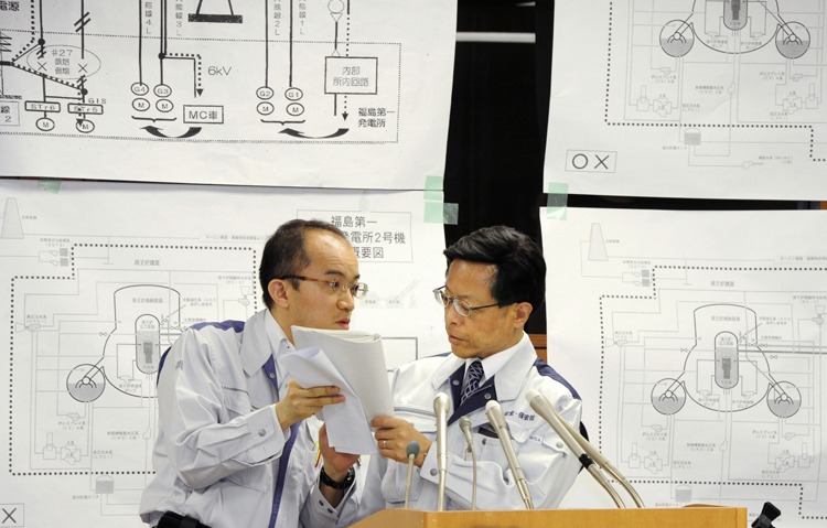 Nuclear and Industrial Safety Agency spokesman Hidehiko Nishiyama, right, huddles with his aide during a press conference on the crippled Fukushima Dai-ichi nuclear complex, in Tokyo today.