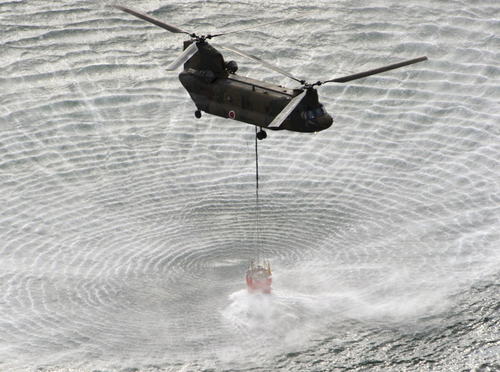 A Japanese Self-Defense Forces helicopter scoops water off Japan's northeast coast on its way to the Fukushima Dai-ichi nuclear power plant in Okumamachi this morning.