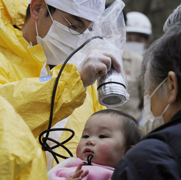 A baby is checked for radiation exposure level in Nihonmatsu in Fukushima prefecture today following a third explosion at the Fukushima Dai-ichi nuclear power complex.