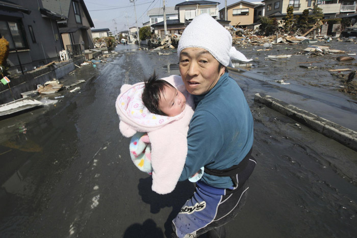 Upon hearing another tsunami warning today, a father tries to flee for safety with his just reunited baby girl who was found by a rescuer in the rubble of tsunami-torn Ishinomaki.