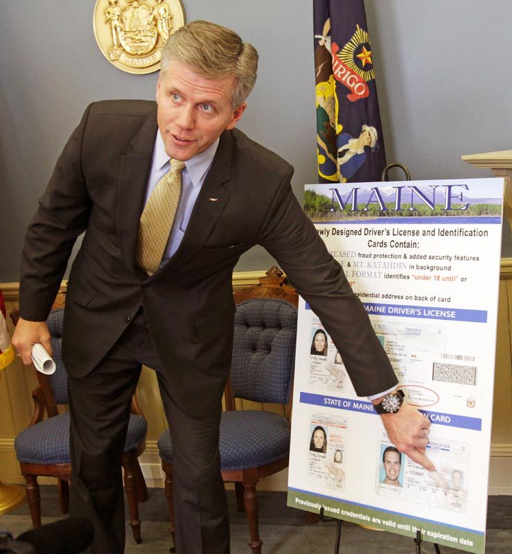 Secretary of State Charlie Summers points to a detail on a poster of the new Maine driver's license design featuring updated security enhancements, at a news conference in Augusta today.