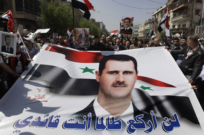 Pro-Syrian President Bashar Assad supporters hold Assad's poster with Arabic words reading: