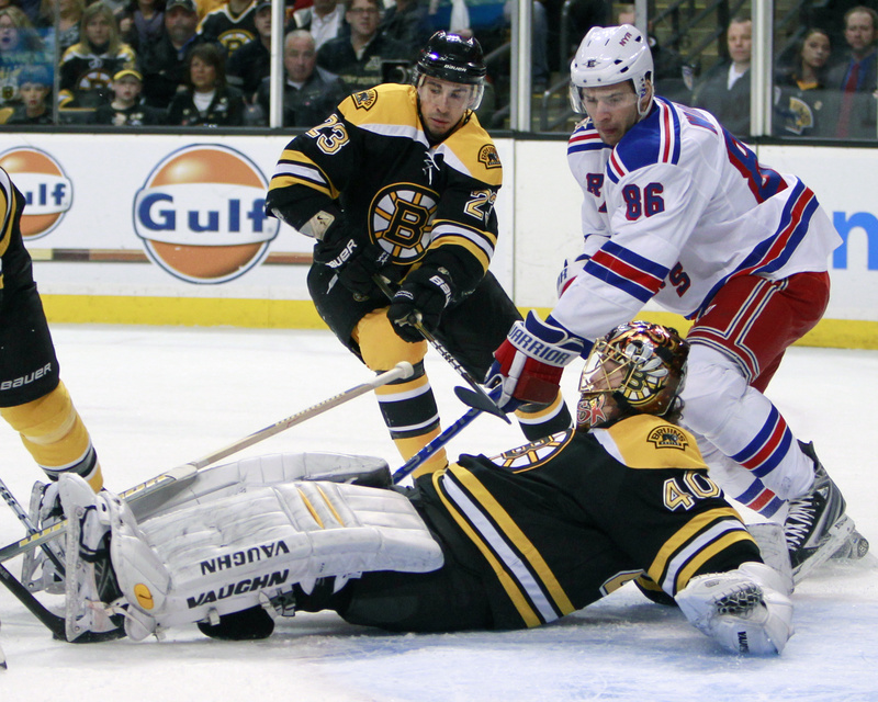 Bruins goalie Tuukka Rask smothers the puck as Wojtek Wolski of the Rangers looks for a rebound in today's game at Boston. The Rangers won, 1-0.