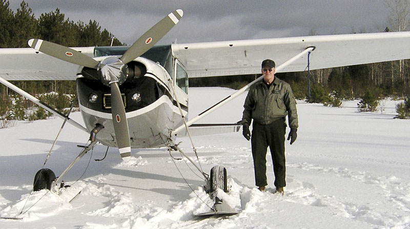 This January 2007 photo released by the Maine Department of Inland Fisheries and Wildlife shows Daryl Gordon standing next to his plane on a frozen lake.