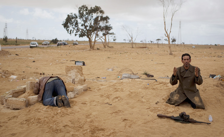 A Libyan rebel prays next to his gun while another kneels over the grave of his dead brother, killed in the fighting, on the outskirts of the city of Ajdabiya, south of Benghazi, Libya, today.