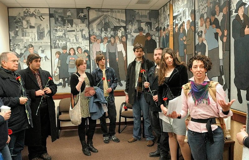 Jessica Graham, of Waterville, right, leads a memorial prayer on the 100th anniversary of the New York Triangle Shirtwaist Factory fire, which killed 146 people as part of an event this morning in front of a mural in the Dept. of Labor lobby in Augusta. This was the first of two events to protest Gov. Paul LePage's order to remove the 36-foot, 11-panel mural Judy Taylor, of Tremont, that was installed there in 2008. There is another scheduled there for noon.