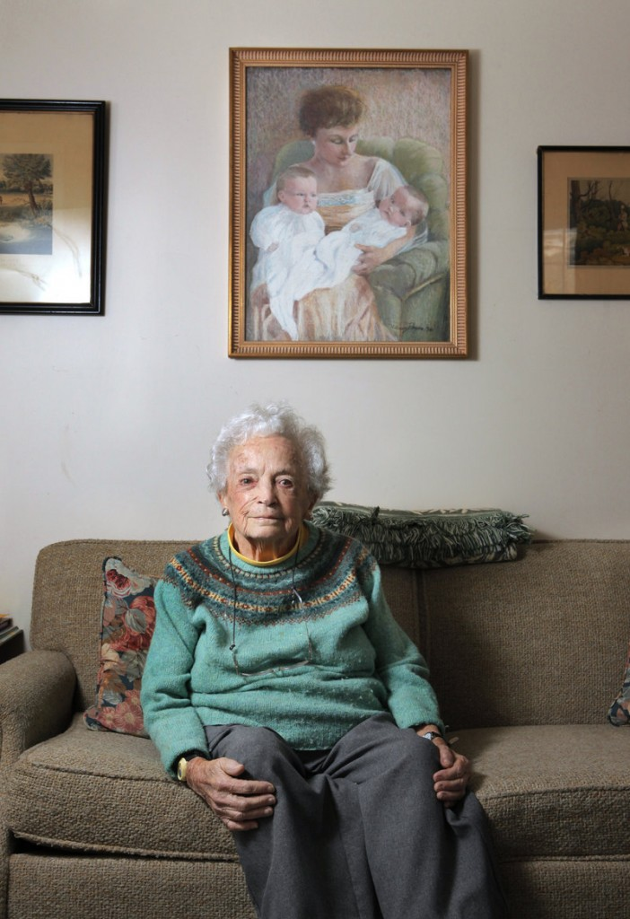 """Nancy Payne of Falmouth poses below a portrait that she painted of her mother holding her and her twin sister, Penelope Dwinell. """"I am compulsively creative,"""" she said."""