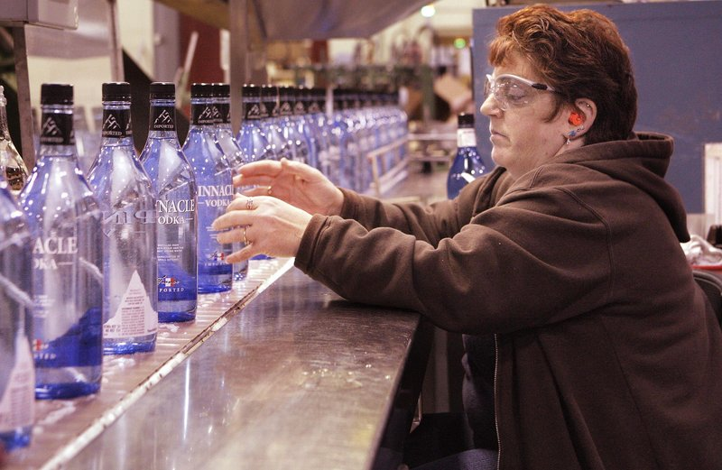 Cynthia Fisher checks labels and the fill levels of bottles of Pinnacle Vodka at White Rock Distilleries in Lewiston.