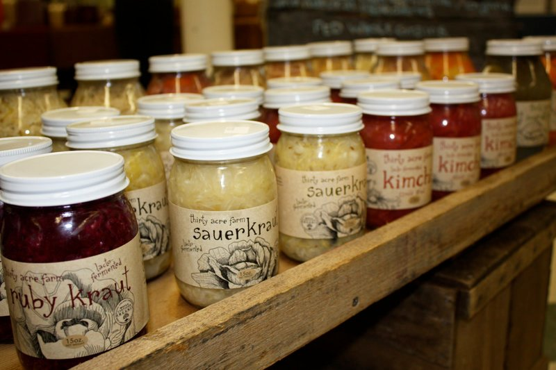 Jars of Thirty Acre Farm sauerkraut, kim chi and pickles sport new labels in this display at the Winter Farmers Market in Portland, thanks to a loan from the No Small Potatoes Investment Club.