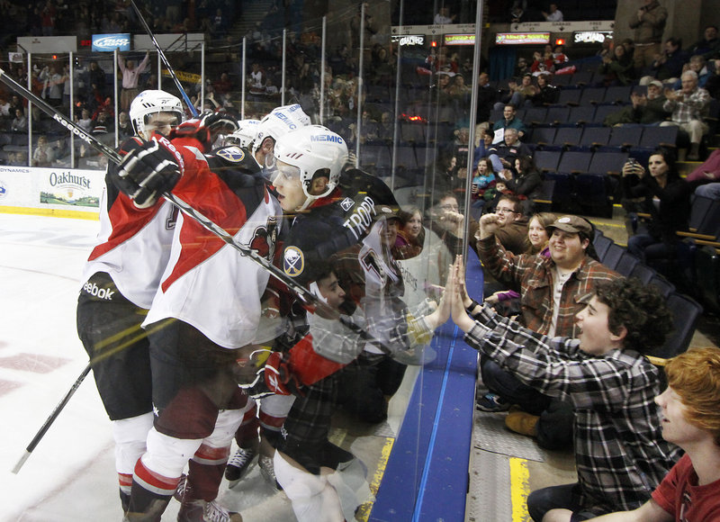 Corey Tropp is mobbed by teammates after scoring a third-period goal that gave the Pirates a 2-1 lead against Hershey on Tuesday night.