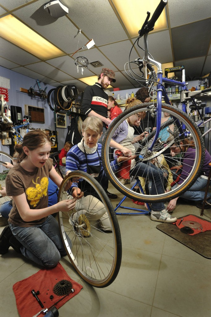 Jamie White, left, and volunteer Alicia Soliman work together on cleaning and replacing the rear hub of a bicycle during a Bike Monkeys class at the Community Bicycle Center.