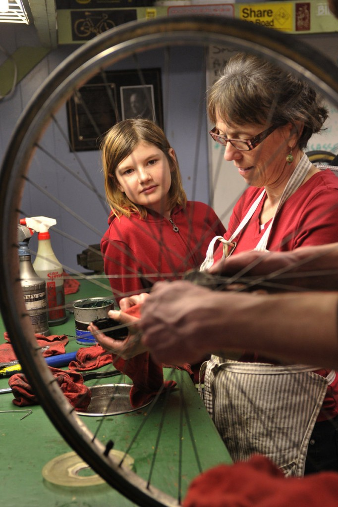 Sophia Hibbard, left, of Windham, and volunteer Karen Nelson are framed by a wheel as they work on a rear hub assembly.