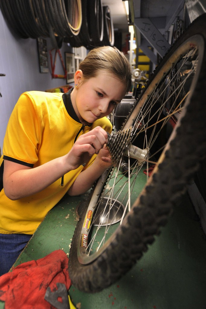 Alexis Gendron, of Biddeford, re-attaches the gear assembly on the rear hub of the bike she's learning to overhaul.