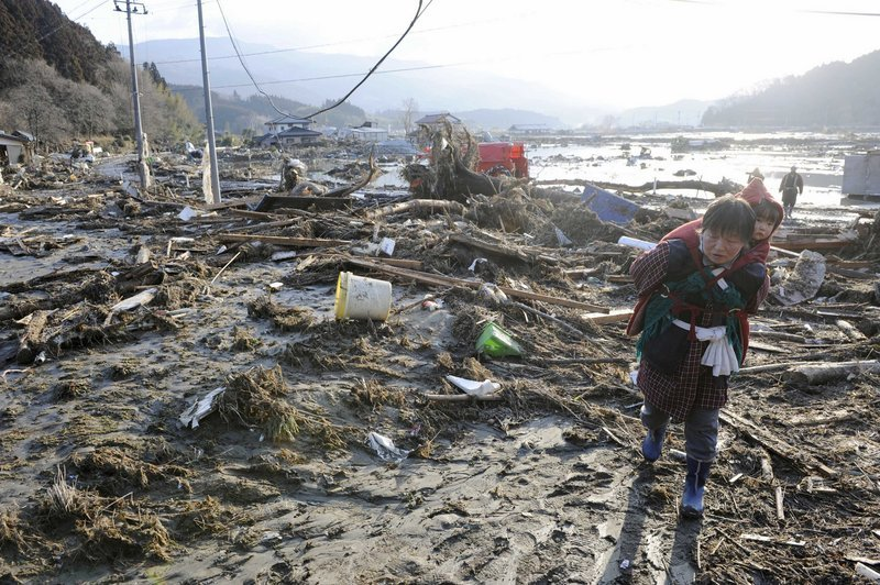 A woman carrying a child walks over debris left by a tsunami that was spawned by the largest earthquake ever recorded in Japan's history.